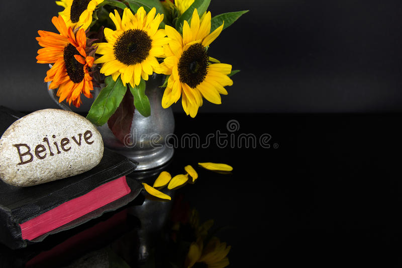 Geloof gesneden in steen op Bijbel met zonnebloemen royalty-vrije stock afbeelding