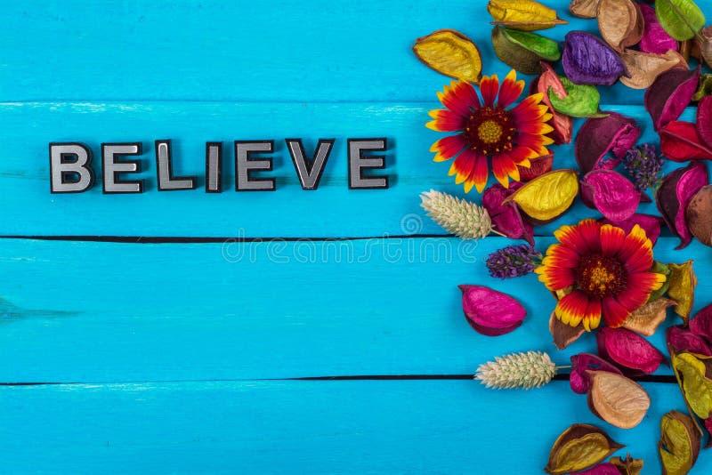 Geloof woord op blauw hout met bloem stock afbeeldingen