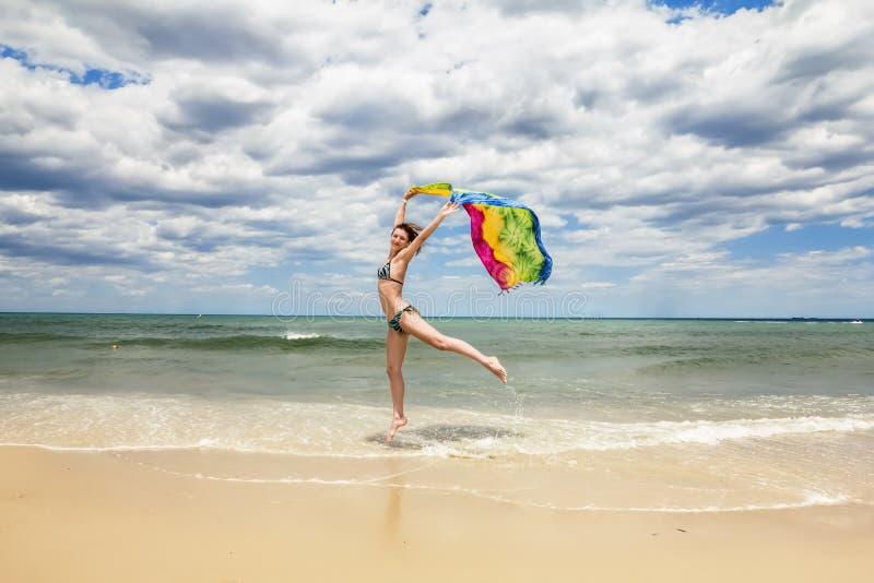 Gelooid meisje die in bikini op het strand met een gekleurde sjaal springen stock foto