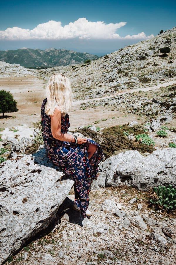 Gelooid meisje in mooie kledingszitting alleen op de steen in het bergachtige landschap van hooglandplatteland van het Grieks royalty-vrije stock afbeeldingen