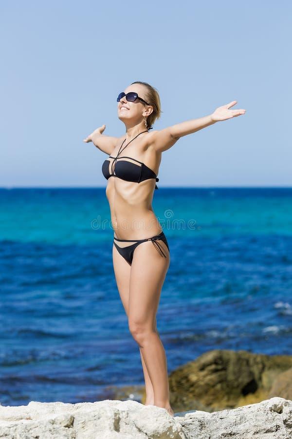 Gelooid meisje in zwempak het stellen met wapens uitgestrekt tegen Se stock afbeelding