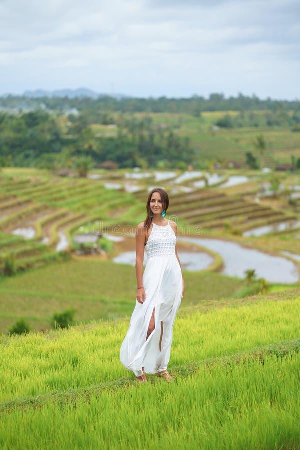 Gelooide mooie vrouw in witte lange kleding die en tegen de achtergrond van padievelden glimlachen stellen stock foto's