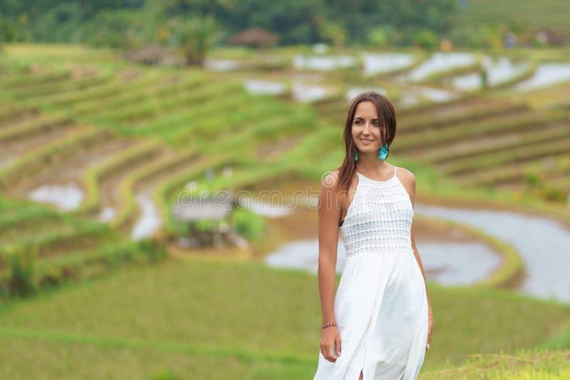 Gelooide mooie vrouw in witte lange kleding die en tegen de achtergrond van padievelden glimlachen stellen Sluit omhoog stock afbeeldingen
