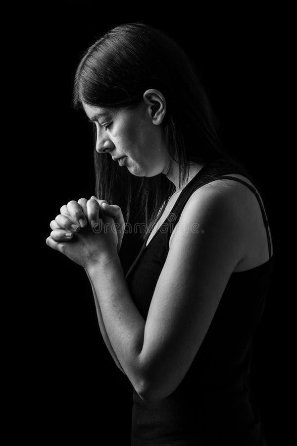 Gelovige vrouw die, handen bidden die in verering aan god worden gevouwen stock foto