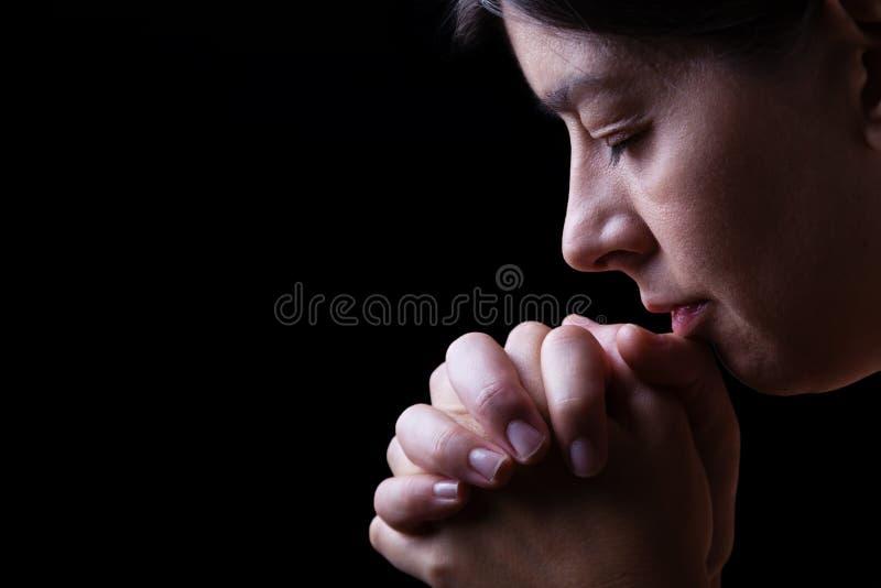 Gelovige vrouw die, handen bidden die in verering aan god worden gevouwen royalty-vrije stock fotografie
