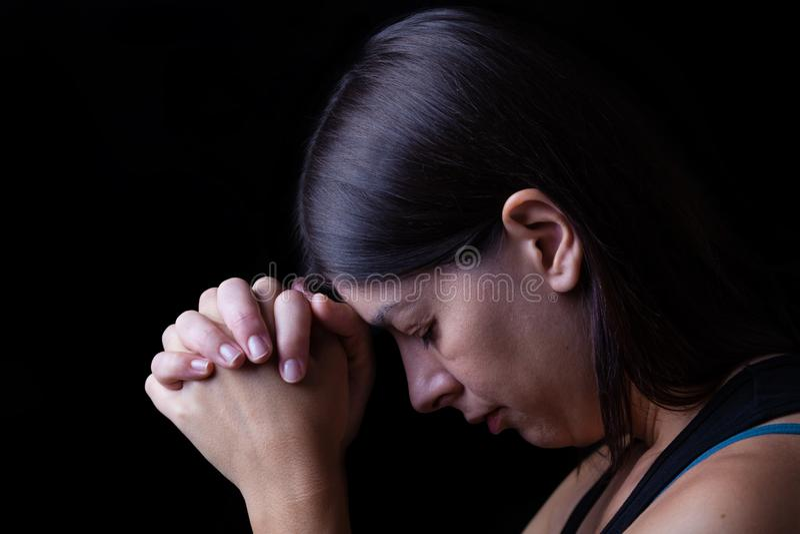 Gelovige vrouw die, handen bidden die in verering aan god worden gevouwen stock afbeelding