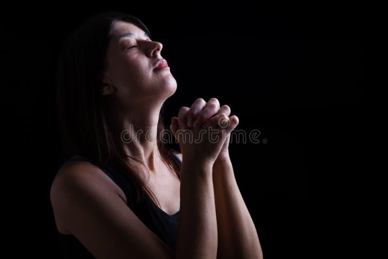 Gelovige vrouw die, handen bidden die in verering worden gevouwen royalty-vrije stock afbeeldingen