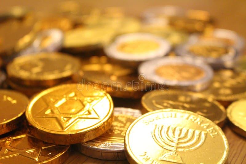 Gelt de Jánuca con la estrella de David de la parte posterior encendido y del símbolo del menorah del judaísmo foto de archivo