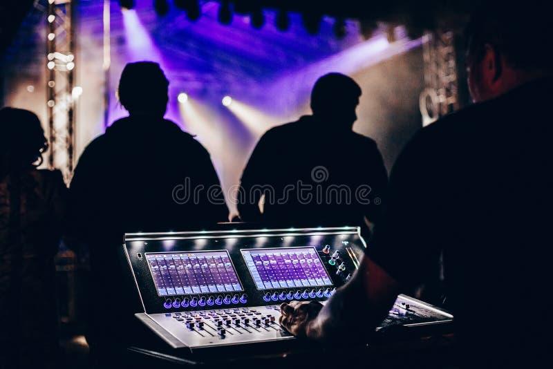Geluidstechnicus controleert professionele audiomixer in concert stock afbeeldingen