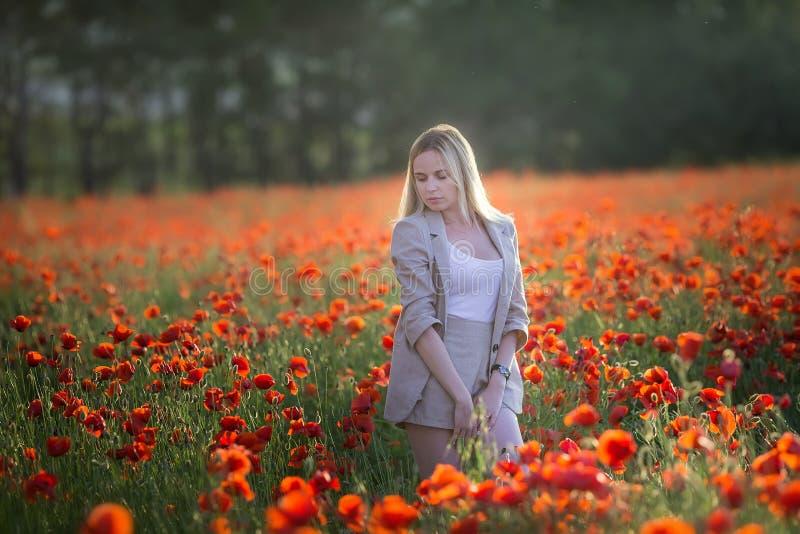 Geluk, aard, de zomer, vakantie en mensenconcept - glimlachende jonge vrouw met gesloten ogen die strohoed op papavergebied drage royalty-vrije stock foto