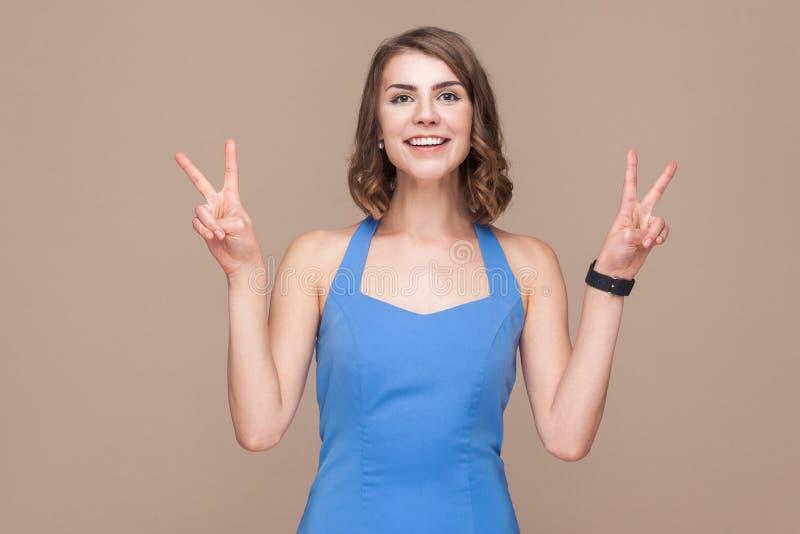 Geluk bedrijfsvrouw die v-teken tonen bij camera en glimlach stock foto's