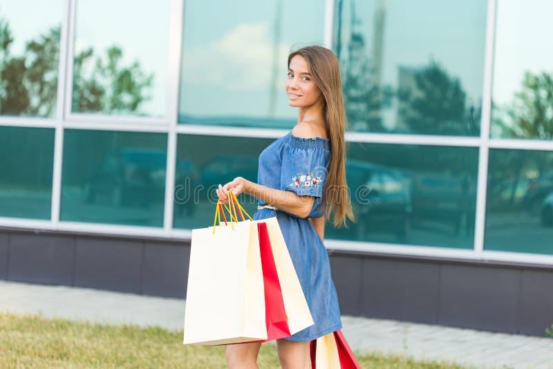 geluk, consumentisme, verkoop en mensenconcept - glimlachende jonge vrouw met het winkelen zakken stock fotografie