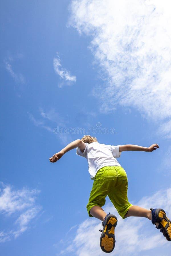 Geluk, kinderjaren, vrijheid, beweging en mensenconcept - gelukkige jongen die in lucht in de blauwe hemel springen royalty-vrije stock afbeelding