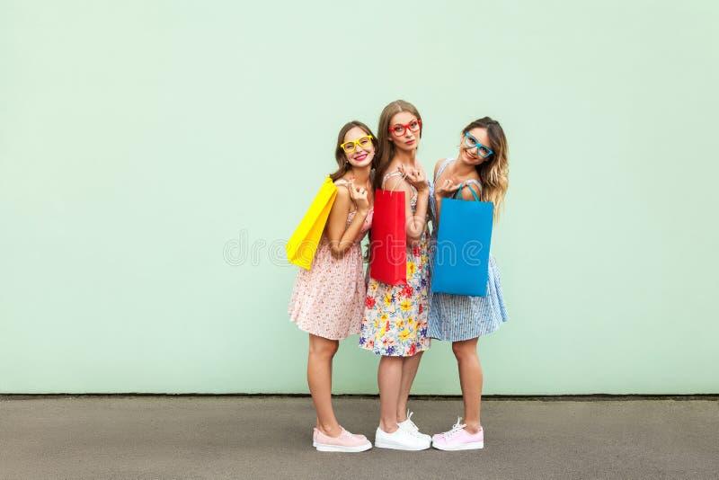 Geluk mooie drie vrienden in glazen met kleurrijke pakketten na het winkelen stock fotografie
