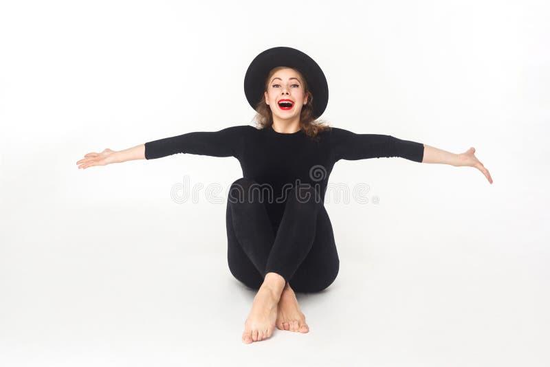 Geluk mooie vrouw in hoed, die op vloer zitten royalty-vrije stock afbeeldingen