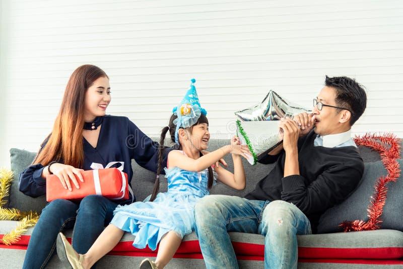 Gelukfamilie die een genietende van partij met giftdozen thuis vieren in woonkamer Vakantiepartij en vieringskerstmis stock afbeeldingen