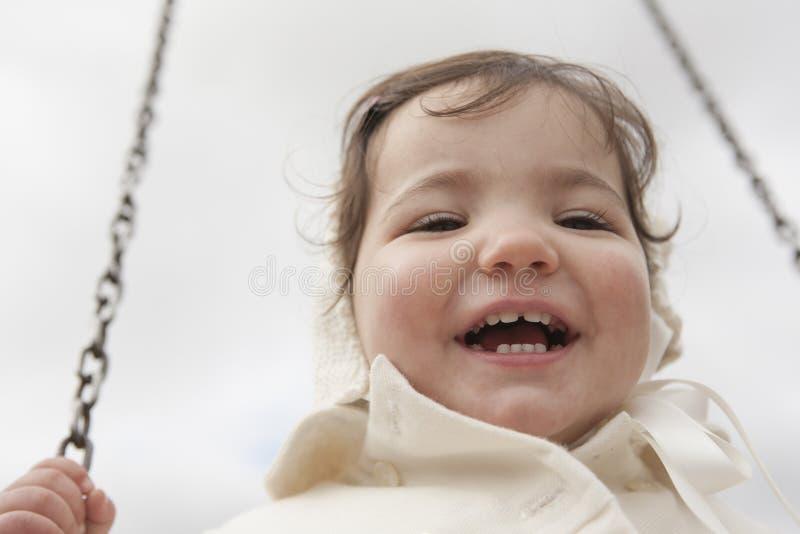 Gelukkig 2 éénjarigenmeisje die pret op een schommeling op de winter hebben royalty-vrije stock foto's