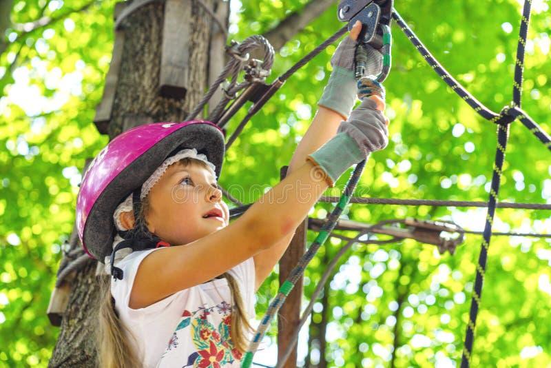 Gelukkig 5 éénjarigenmeisje in roze beschermende helm en materiaal in een kabelpark in de zomer stock afbeelding