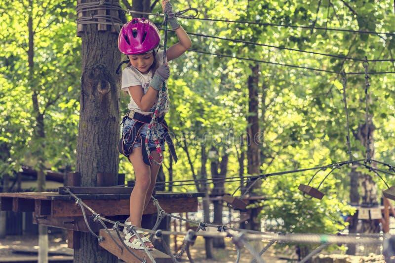 Gelukkig 5 éénjarigenmeisje in roze beschermende helm en materiaal in een kabelpark in de zomer stock fotografie