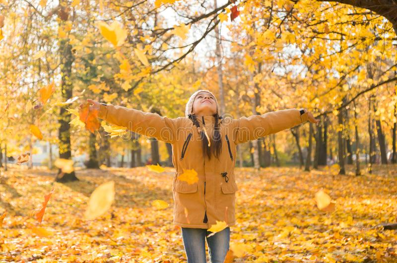 Gelukkig aanbiddelijk meisje die de gevallen bladeren werpen die omhoog, in het de herfstpark spelen royalty-vrije stock afbeelding