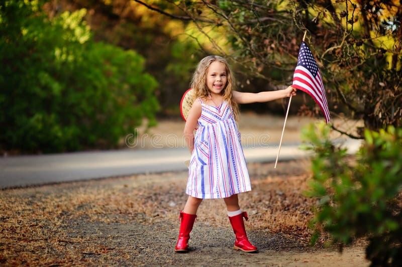 Gelukkig aanbiddelijk meisje die en Amerikaanse vlag glimlachen golven outs royalty-vrije stock foto