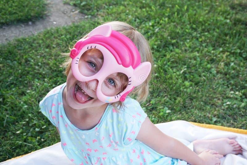 Gelukkig aanbiddelijk meisje die grappig gezicht met masker op het maken royalty-vrije stock foto