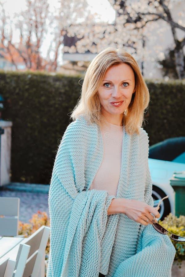 Gelukkig aantrekkelijk blij die blondemeisje in lichtblauwe gebreide warme plaid wordt verpakt die en camera in haar tuin glimlac royalty-vrije stock afbeelding