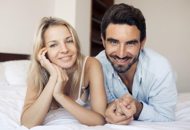 Gelukkig aantrekkelijk glimlachend paar die op bed in slaapkamer liggen stock fotografie