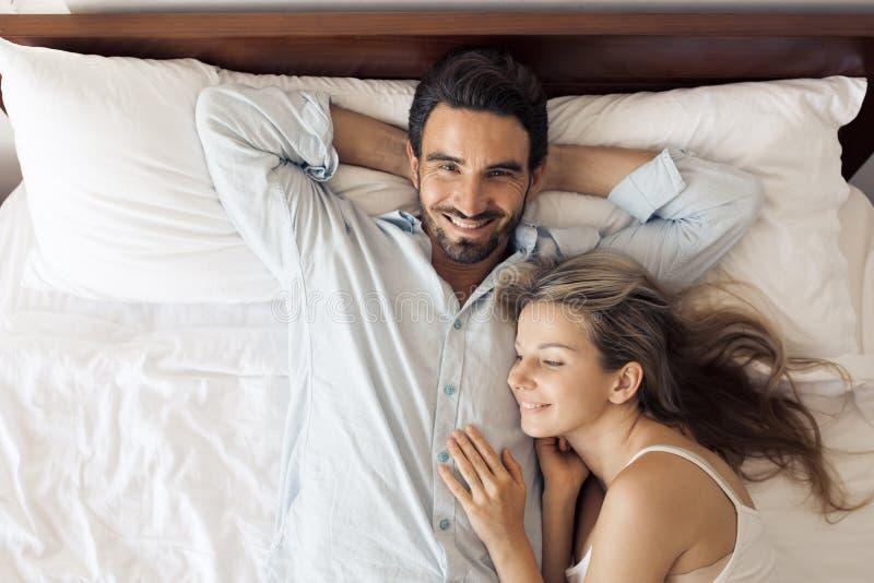 Gelukkig aantrekkelijk glimlachend paar die op bed in slaapkamer liggen royalty-vrije stock foto's