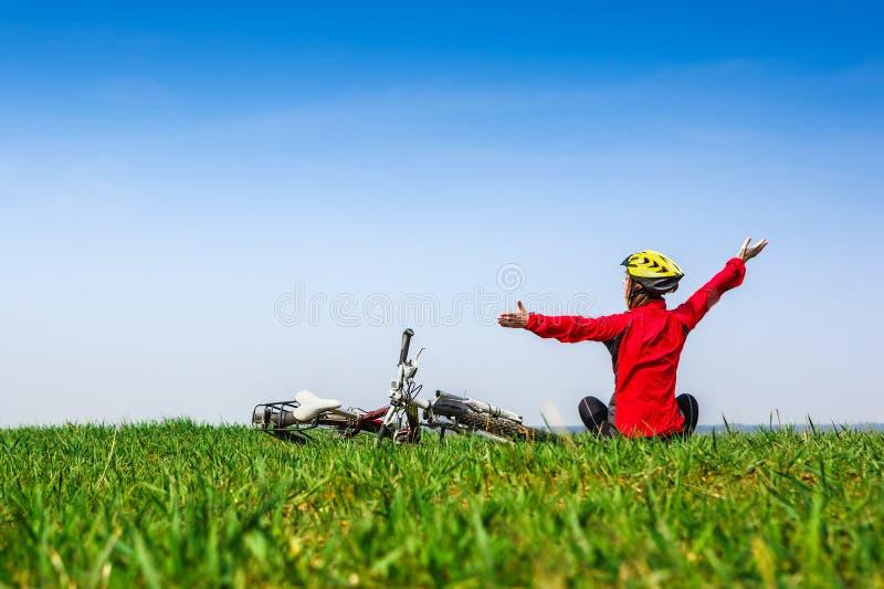 Gelukkig actief meisje die met fiets van de mening over een groene weide genieten stock foto's