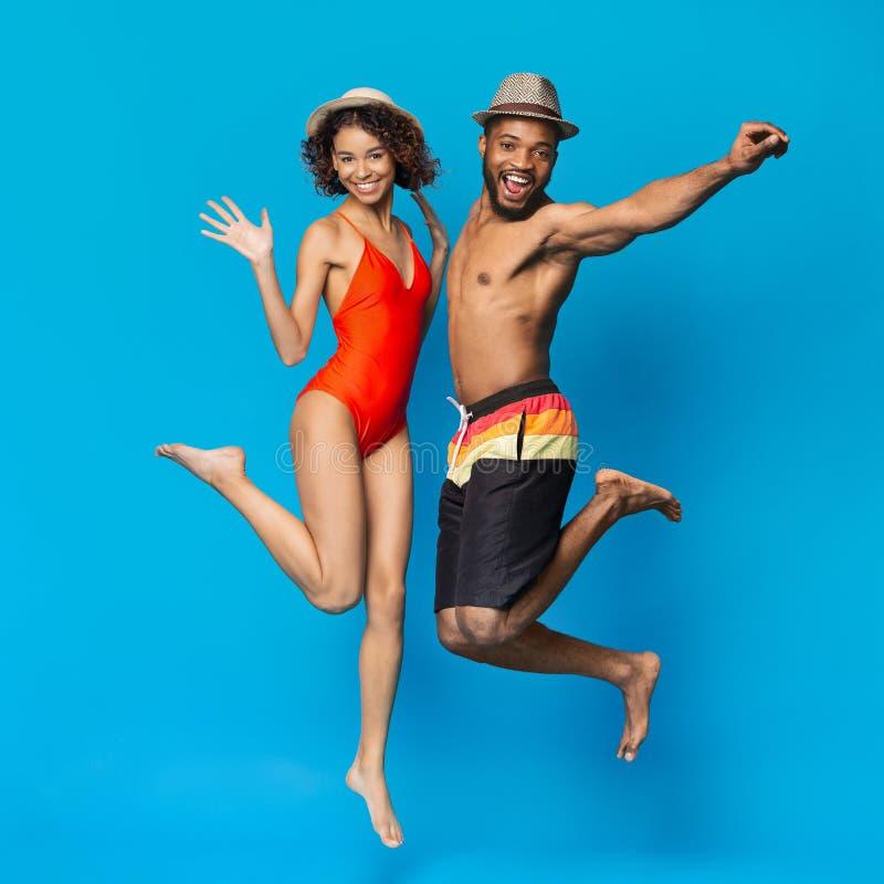 Gelukkig Afrikaans Amerikaans Millennial Paar die in Swimwear in Lucht springen stock foto's