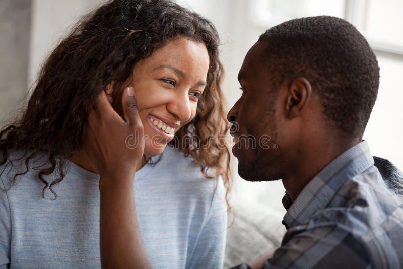 Gelukkig Afrikaans Amerikaans paar die datum hebben thuis stock fotografie