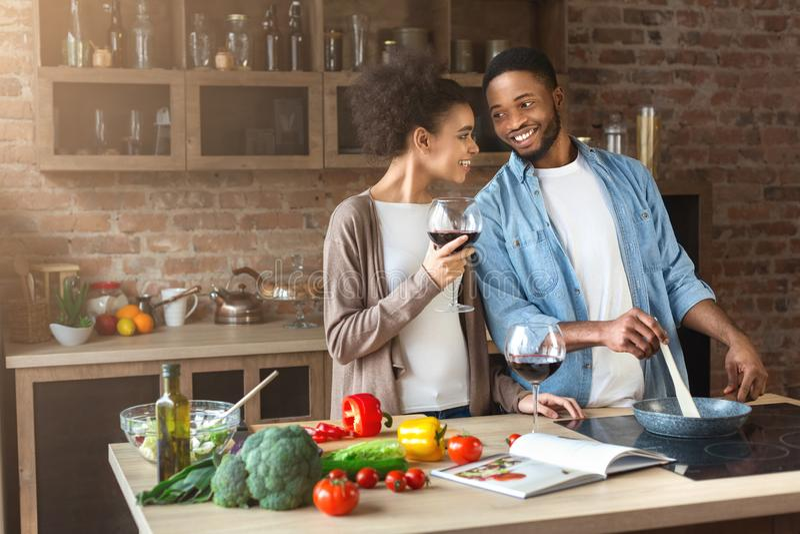 Gelukkig Afrikaans-Amerikaans paar die en rode wijn koken drinken royalty-vrije stock foto's