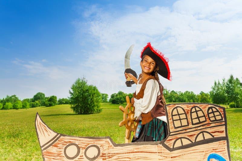 Gelukkig Afrikaans meisje als piraat met hoed en zwaard stock afbeeldingen