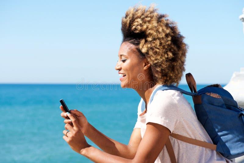 Gelukkig afro Amerikaans wijfje die zich in openlucht en op mobiele telefoon texting bevinden royalty-vrije stock foto