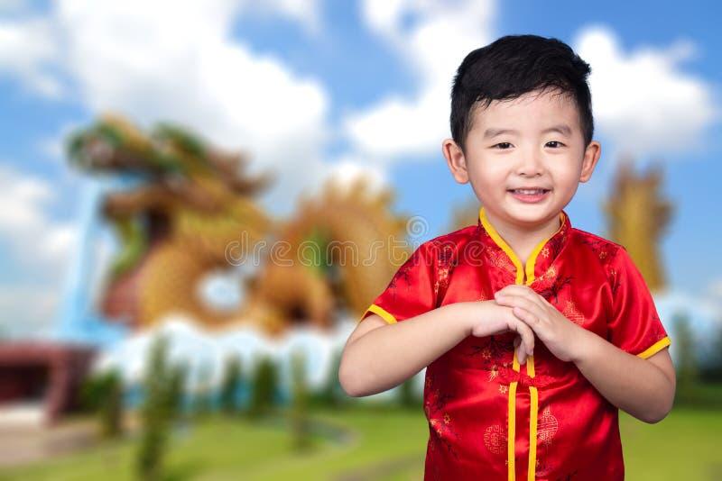 Gelukkig Aziatisch Chinees jong geitje die rood traditioneel kostuum op Chinese tempel of joss huisviering dragen als achtergrond stock foto's