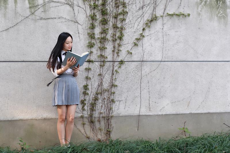 Gelukkig Aziatisch Chinees mooi de studentenkostuum van de meisjesslijtage in school die en een boek in aard in de lente glimlach royalty-vrije stock afbeeldingen
