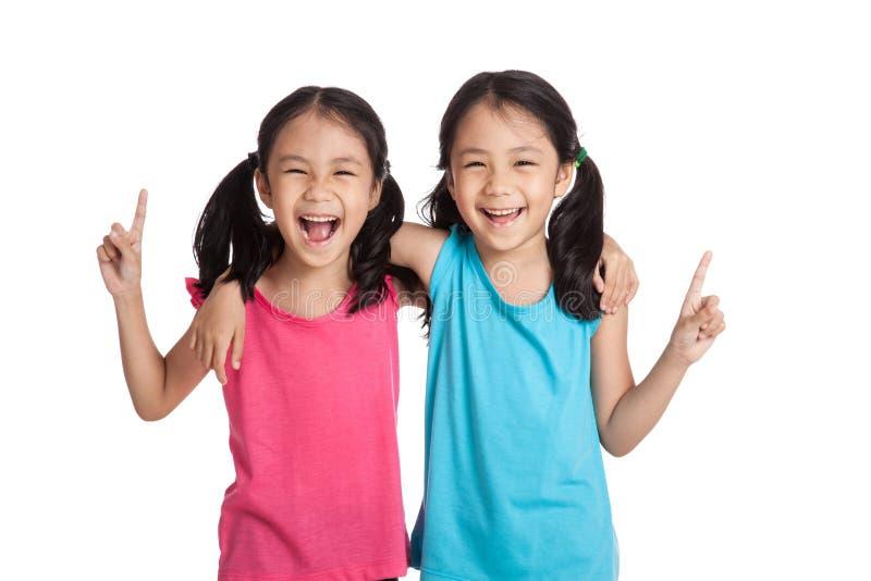 Gelukkig Aziatisch de glimlachpunt van tweelingenmeisjes omhoog stock foto