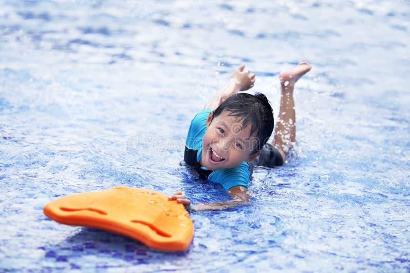 Gelukkig Aziatisch jong geitje bij zwembad stock foto
