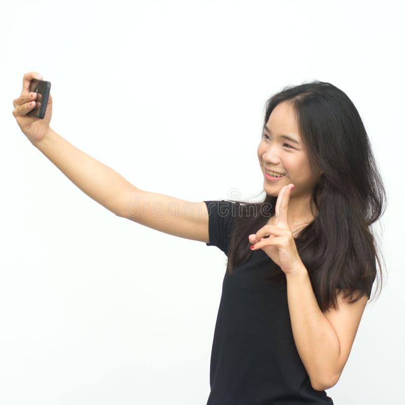 Gelukkig Aziatisch jong meisje die twee vingers richten royalty-vrije stock fotografie