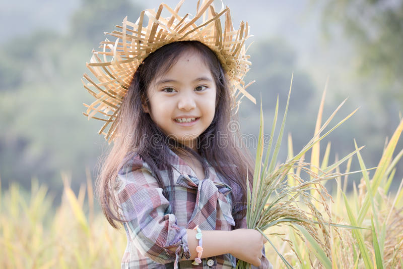 Gelukkig Aziatisch kind in padieveld stock foto's