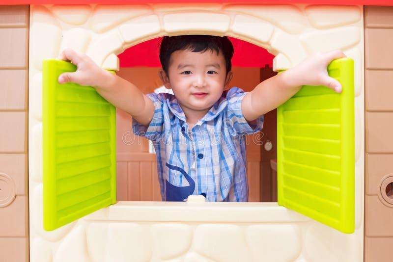 Gelukkig Aziatisch kindjongen het spelen vensterstuk speelgoed huis in speelplaats stock afbeeldingen