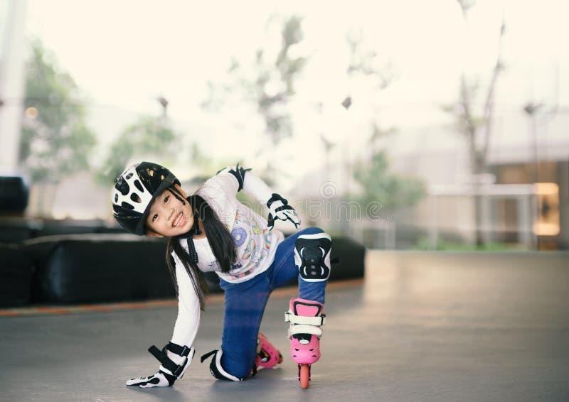 Gelukkig Aziatisch meisje die aan rolschaats leren Kinderen die beschermingsstootkussens voor veilige rit dragen Actieve openluch royalty-vrije stock fotografie