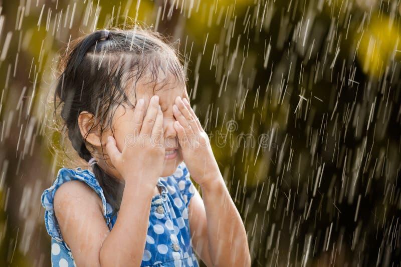 Gelukkig Aziatisch meisje die pret met de regen hebben te spelen royalty-vrije stock fotografie