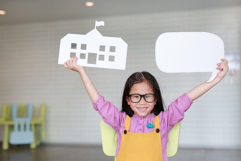 Gelukkig Aziatisch meisje die in roze-gele grove calico's prototypedocument school en lege lege toespraakbel houden om iets binne royalty-vrije stock fotografie