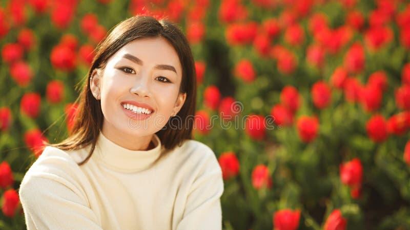 Gelukkig Aziatisch meisje die in tulpentuin aan camera glimlachen royalty-vrije stock foto's