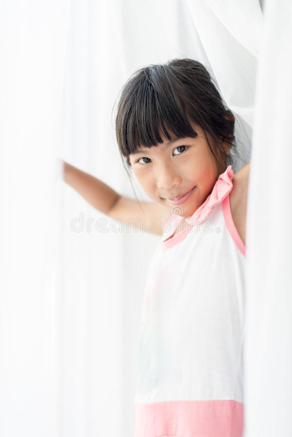 Gelukkig Aziatisch meisje die wit gordijn thuis houden royalty-vrije stock afbeelding