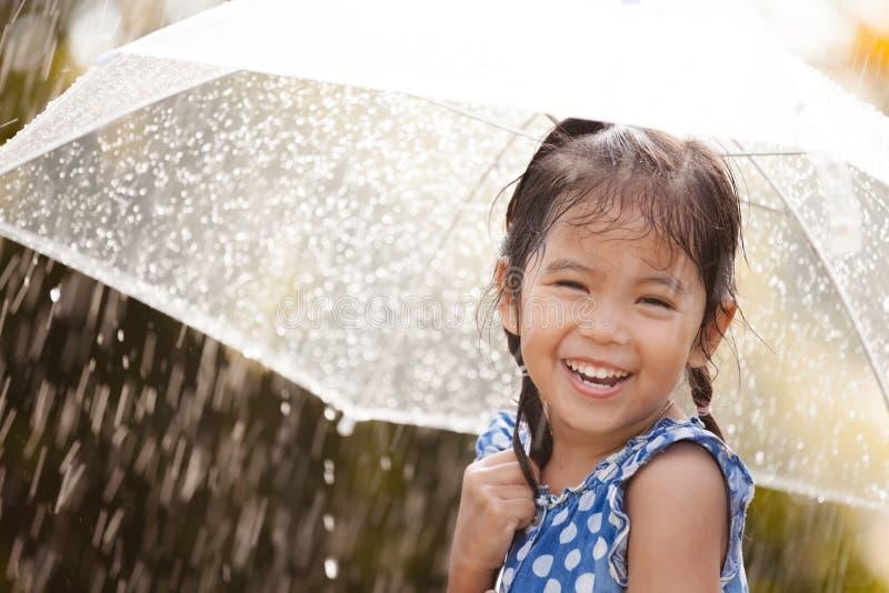 Gelukkig Aziatisch meisje met paraplu in regen stock afbeeldingen