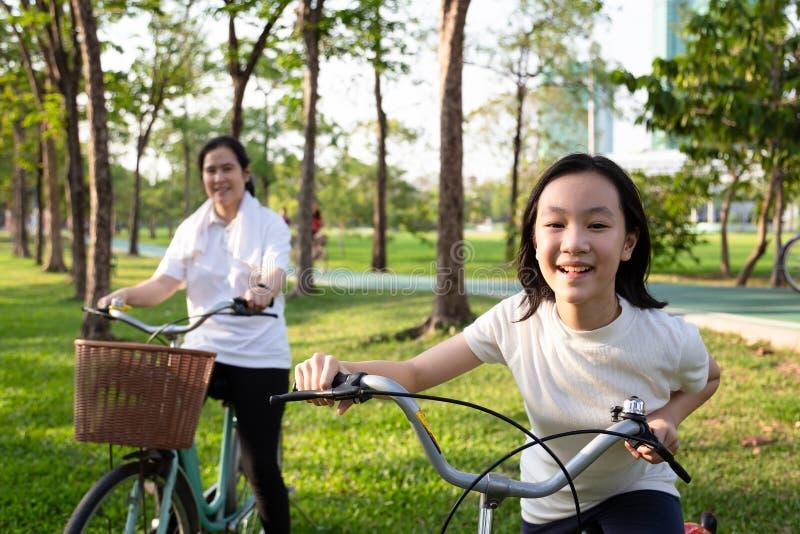 Gelukkig Aziatisch meisjekind met fiets in openluchtpark, glimlachende dochter met moeder op een fietsrit samen, familieactivitei royalty-vrije stock afbeelding