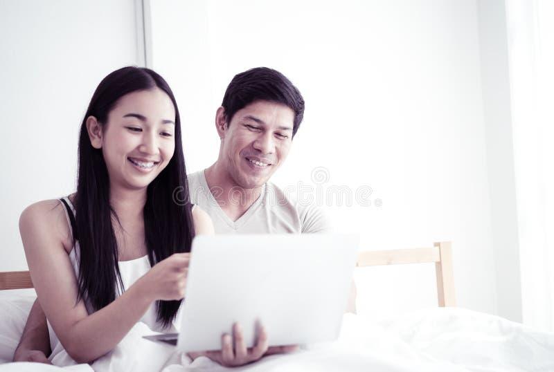 Gelukkig Aziatisch paar die laptop op ochtendbed met behulp van met glimlach royalty-vrije stock afbeelding